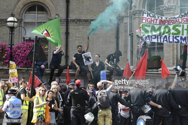 Anti fascism protesters hold flags and a burning flare during the rally Robinson supporters gathered outside BBC to demand the freedom of their...