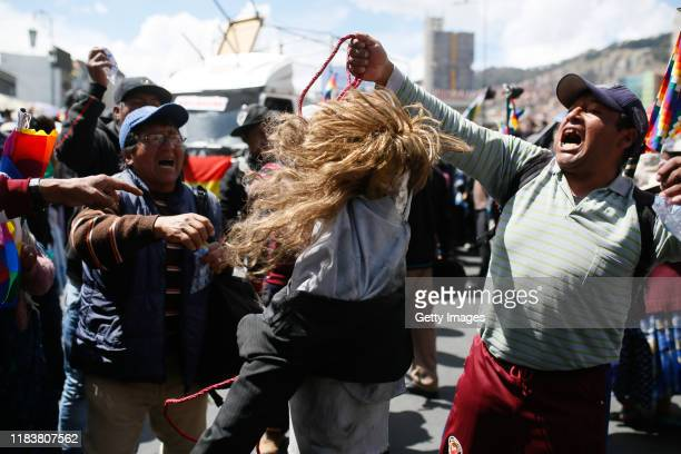 Anti government demonstrators hold a puppet depicting interim president of Bolivia Jeanine Áñez as they shout during a funeral procession of the...