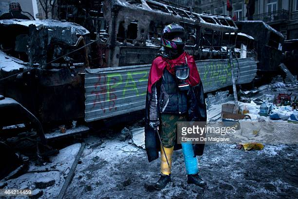 Anti government protester stand next of a charred police truck during standoff with riot units on Hrushevskoho street after consecutives nights of...