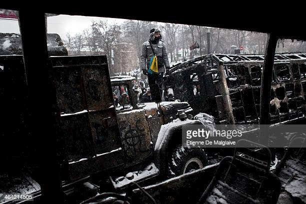 Anti government protesters stand on barricades and charred police trucks during standoff with riot units on Hrushevskoho street after consecutives...