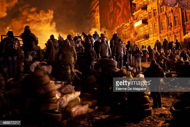Anti government protesters watch clashes with riot polic in late night from a barricade on Hrushevskoho street on January 24 2014 in Kiev Ukraine...