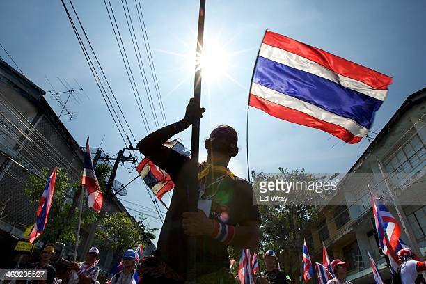 Anti government protesters wave Thai flags during a march shortly before an explosive device went off nearby wounding more than 20 people on January...