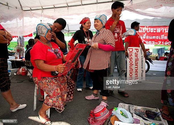 Anti Government Red Shirt supporters of ousted premier Thaksin Shinawatra color their hair at a makeshift hair saloon in the Red compound as the...