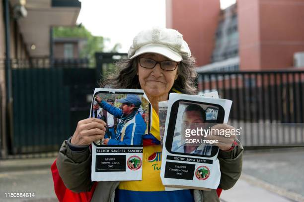 Anti Ivan Duque's demonstrator is seen holding a placard with the photos of social leader Alirio Sánchez Sánchez and the indigenous Hector Janer...