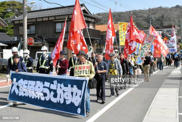Anti nuclear protesters march on near Kansai Electric Power Co's Oi Nuclear Power Plant on March 14 2018 in Oi Fukui Japan The No 3 reactor of the...