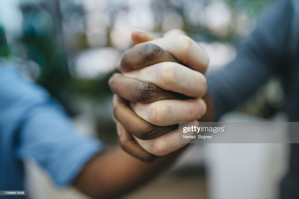 Anti racist studio shot of unrecognizable group of people holding hands : Stock Photo