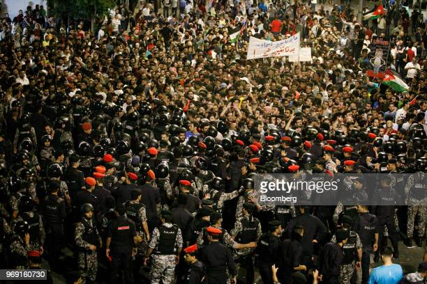 Anti riot police and security forces block the path of protesters during a demonstration against a draft income tax law near the prime minister's...