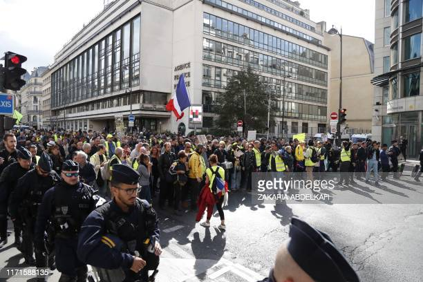 """Anti riot police face """"Yellow vest"""" protesters holding a French flag during an anti-government """"yellow vests"""" protest in front of the Agence France..."""