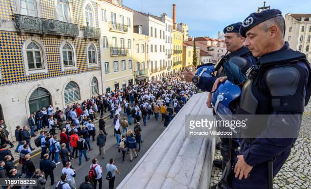 Anti riot police officers give thumbsup to members of Portuguese Police PSP and National Republican Guard GNR marching from Praça Marques de Pombal...
