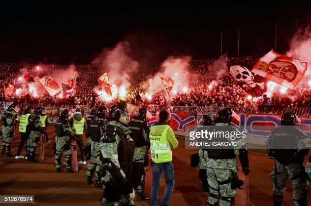 Anti riot police officers stand guard as Red Star's supporters burn torches during the Serbian National soccer league derby match between Partizan...