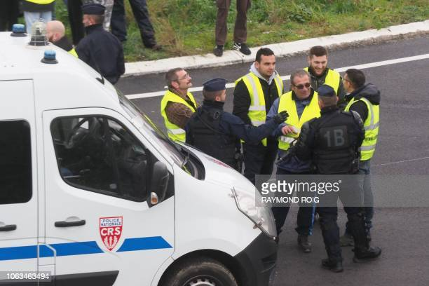 Anti riot police talk with Yellow Vests as they block the road during a demonstration against the rising of the fuel and oil prices on November 19...