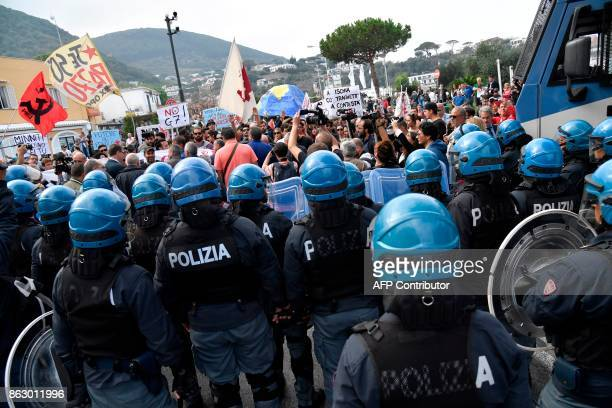 Anti riot policemen face antiG7 protesters in the port of Italian island Ischia on October 19 2017 before the start the G7 summit of Interior...