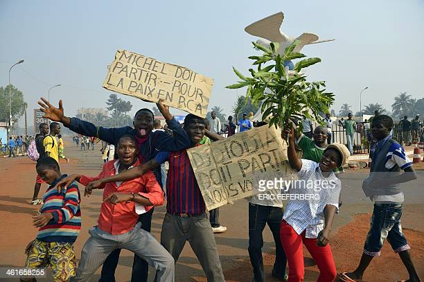 Anti Seleka demonstrators pose with placards reading 'Michel must leave' 'Djotodia must leave we want peace' as they march to Mpoko airport on...