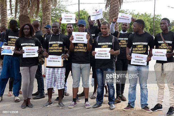 Anti slavery militants demonstrate on August 3 2016 in Dakar against the imprisonement of fellow activists in Mauritania as they hold placards with...