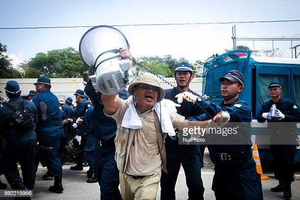 Anti US base leader Hiroji Yamashiro being removed by police after staging a sitin protest protest against the construction of helipads in front of...