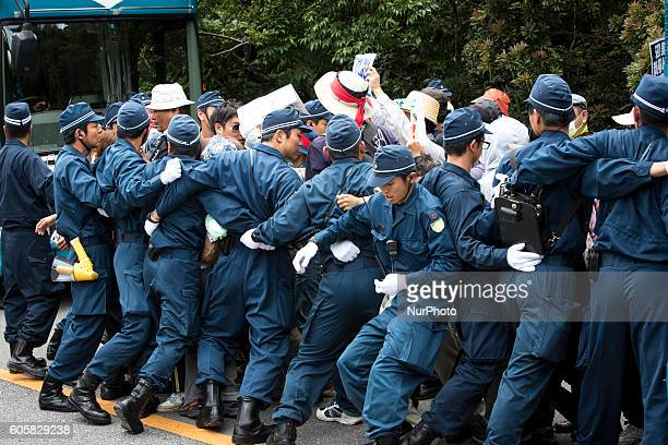 Anti US base protesters is seen being guarded by police after blocking the trucks to protest against the construction of helipads in front of the...