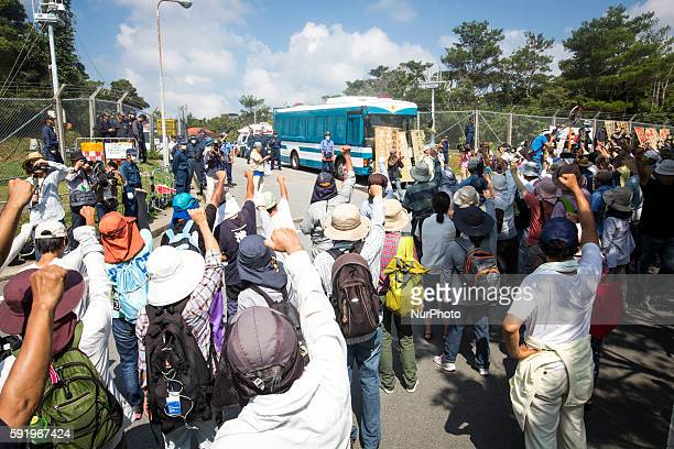 Anti US base protesters raise their fists in the air to protest against the construction of helipads in front of the main gate of US military's...
