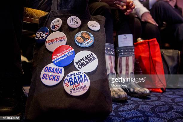 Anti US President Barack Obama buttons hang on a bag in front of attendees listening to Senator Ted Cruz a Republican from Texas not pictured speak...