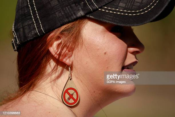Anti vaxxer wearing anti vaccination earrings takes part during the protest. Protesters gather outside Indiana Governor Eric Holcomb's mansion in the...