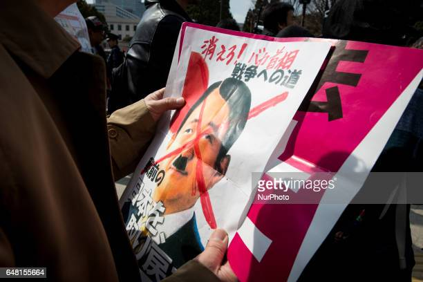 AntiAbe protester holding a placard reading quotGET OUT IDIOT PM ABE BRING BACK OUR PREVIOUS JAPAN gather in front of the National Diet Building to...