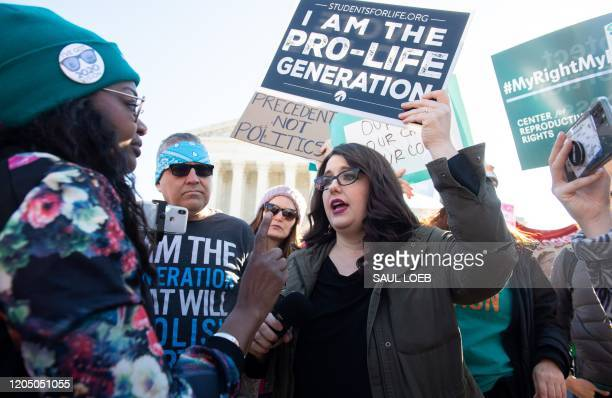 Anti-abortion protesters and pro-choice activists supporting legal access to abortion protest speak to each other during a demonstration outside the...