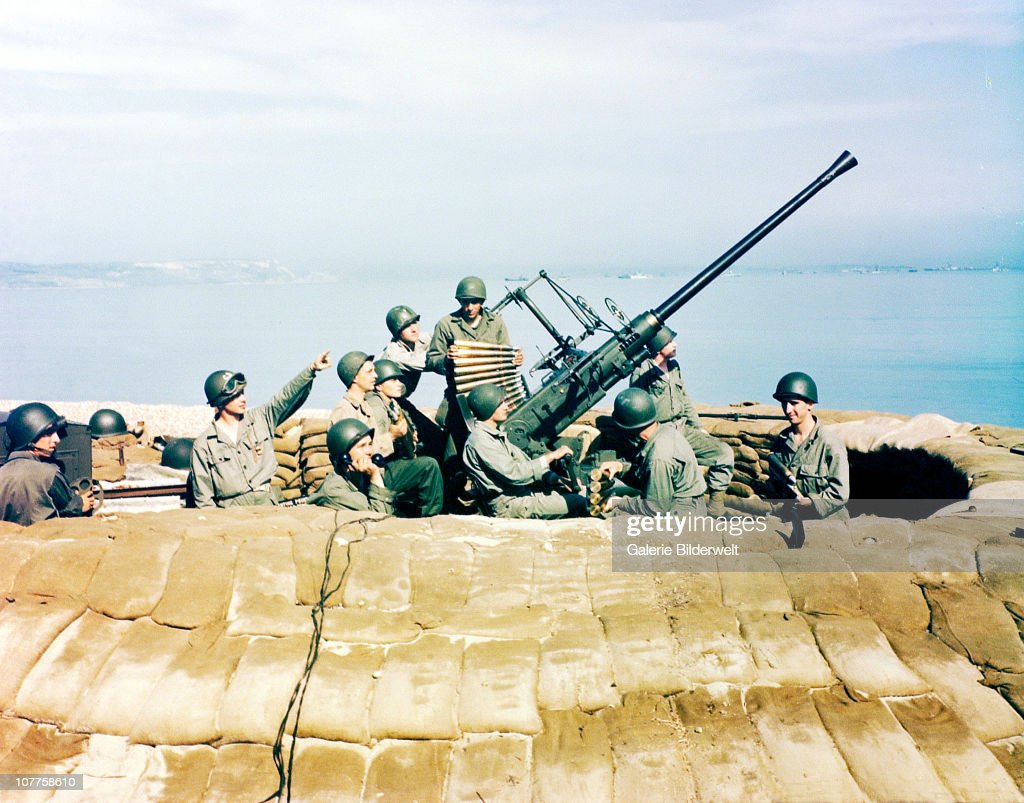 Anti-aircraft Bofors Crew, An American GI is loading a Bofors 40mm antiaircraft gun on the coast of England. June 1944. The last massive German Luftwaffe attack had taken place in London, January 1944. Great Britain.