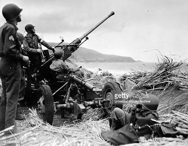 Antiaircraft bofors gun in at position on a mound overlooking the beach in Algeria with a United States antiaircraft artillery crew in position...