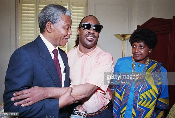 Antiapartheid activist Nelson Mandela greets singer Stevie Wonder as Mandela's wife Winnie looks on Mandela is touring the United States following...