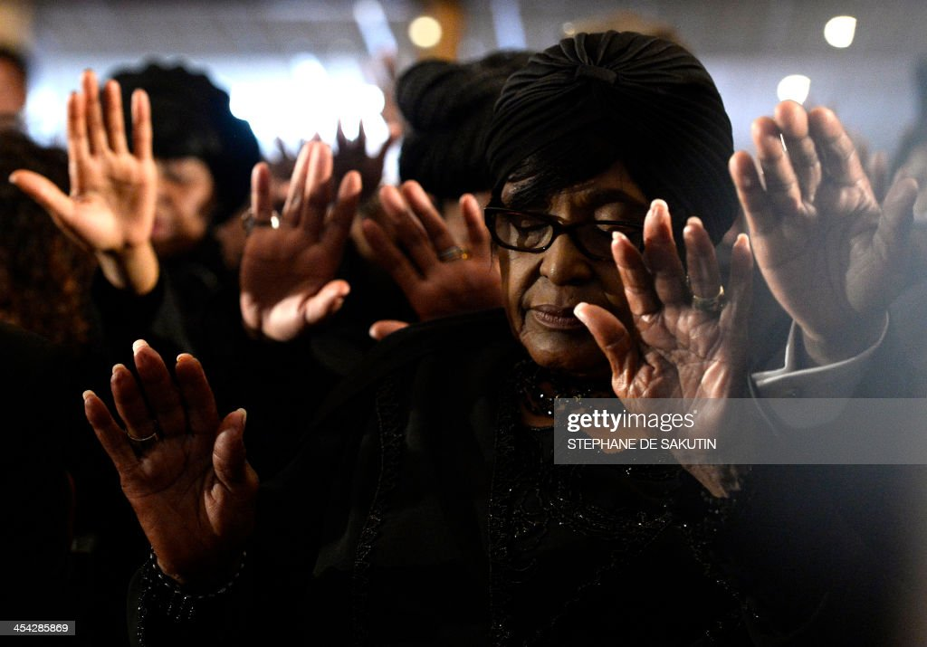 anti-apartheid campaigner Winnie Mandela Madikizela, ex-wife of late President Nelson Mandela, prays during a mass in memory of Nelson Mandela on December 8, 2013 in Johannesburg. The revered icon of the anti-apartheid struggle in South Africa and one of the towering political figures of the 20th century, died in Johannesburg on December 5 at age 95. Mandela, who was elected South Africa's first black president after spending nearly three decades in prison, had been receiving treatment for a lung infection at his Johannesburg home since September, after three months in hospital in a critical state. AFP PHOTO / STEPHANE DE SAKUTIN / AFP PHOTO / Stéphane DE
