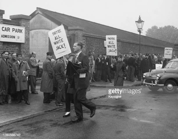 Anti-apartheid demonstrators carrying placards reading 'They're All White Jack!' on the day the Second Test between England and South African was due...