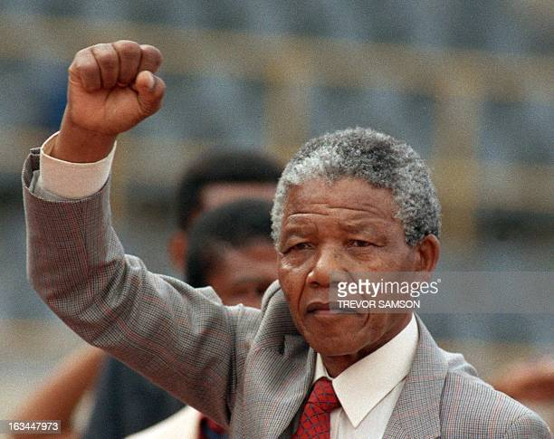 Anti-apartheid leader and African National Congress member Nelson Mandela raises clenched fist, arriving to address mass rally, a few days after his...