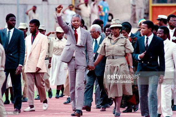 Antiapartheid leader and African National Congress member Nelson Mandela raises clenched fist accompanied by his wife antiapartheid campaigner Winnie...