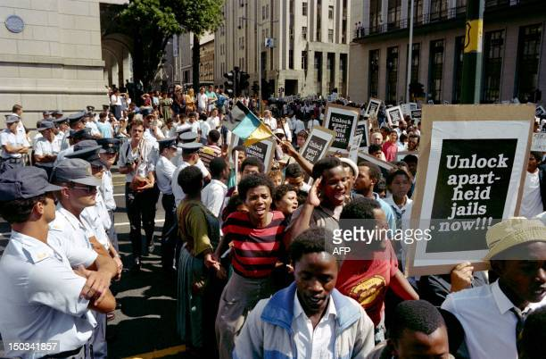 AntiApartheid marchers pass by policemen as they demonstrate to demand the release of all the political prisoners in South Africa on February 02 1990...
