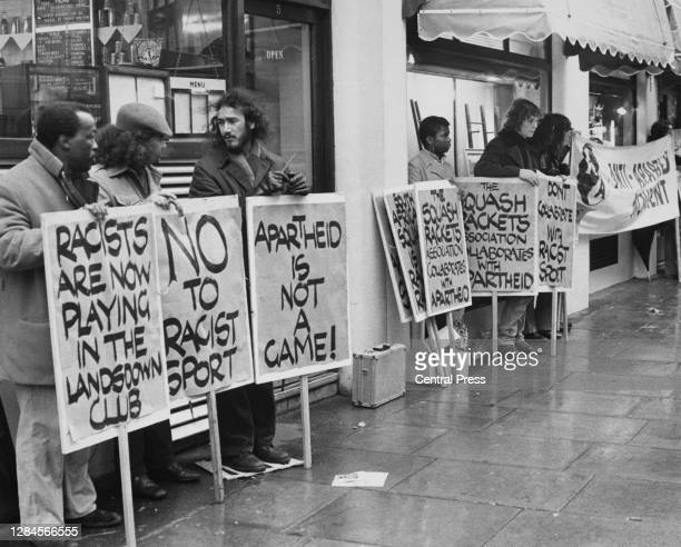 Anti-Apartheid protestors hold placards reading 'Racists are now playing in the Lansdowne Club', 'No to racist sport', 'Apartheid is not a game' and...
