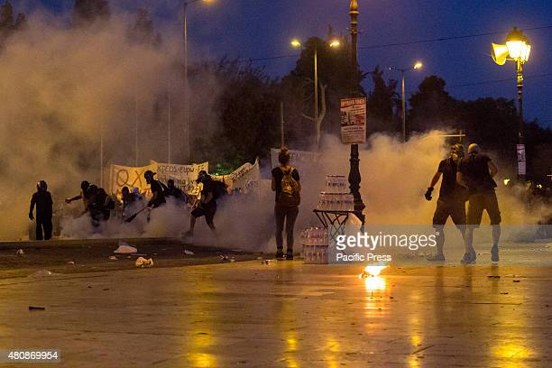 Antiauthoritarians covered with smoke from tear gas bombs thrown by riot policemen Unions gather in Syntagma square to protest against the voting of...