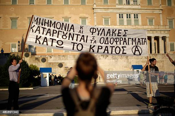 Antibailout protestors hold up a banner outside the Greek parliament during a demonstration in central Athens Greece on Wednesday July 15 2015 Greek...