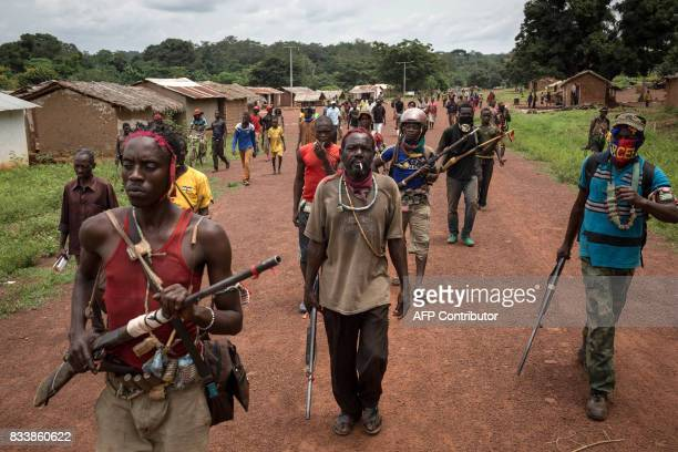 TOPSHOT Antibalaka fighters walk in Gambo southeast Central African Republic on August 16 2017 Antibalaka fighters fought against a Seleka militia to...