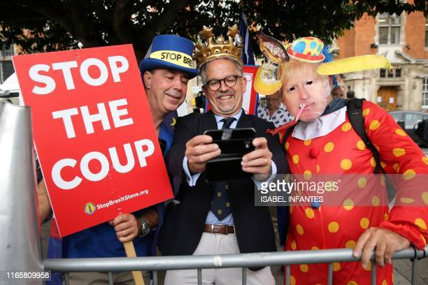 AntiBrexit activist Steve Bray stands with Dr David Nicholl and an activist dessed as a clown and wearing a mask depicting Britian's Prime Minister...