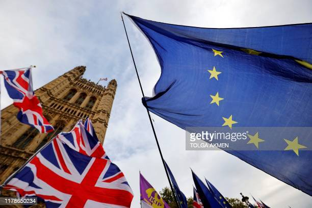 TOPSHOT AntiBrexit activists' EU flags are pictured alongside the Union flags of proBrexit activists as they demonstrate outside of the Houses of...