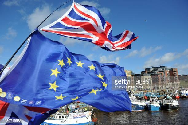 AntiBrexit activists fly EU flags as fishing boats take part in a demonstration on the River Tyne in Newcastle northeast England on March 15 against...