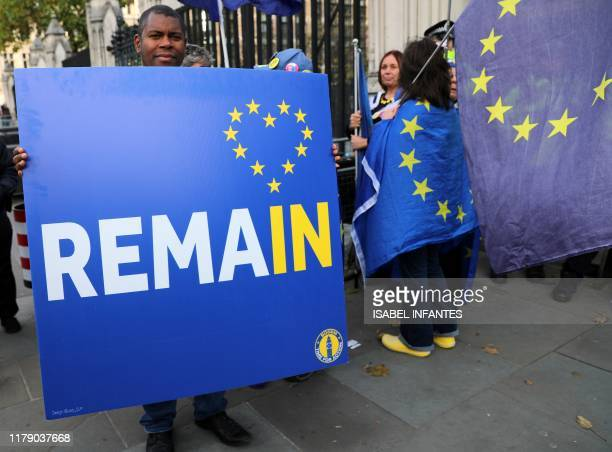 AntiBrexit activists hold banners and wave EU flags as they demonstrate outside the Houses of Parliament in London on October 30 2019 Prime Minister...