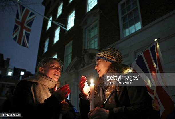 AntiBrexit activists hold candles as they stand beneaath the Union floag hanging outside Europe House in central London on January 31 during a...