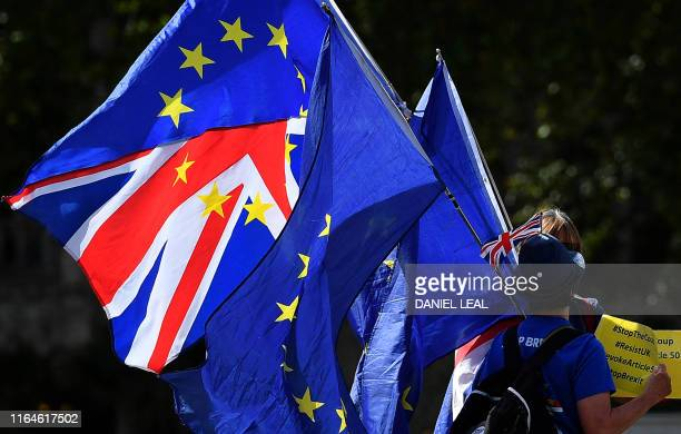 TOPSHOT AntiBrexit activists hold Union and EU flags as they demonstrate opposite the Houses of Parliament in Westminster London on August 29 2019...