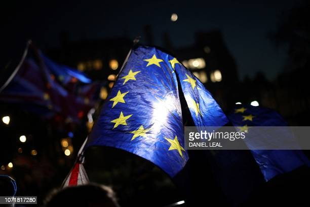 AntiBrexit activists wave Union and European Union flags as they protest outside the Houses of Parliament in London on December 11 2018 British Prime...