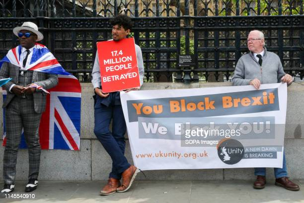 Anti-Brexit and Pro-Brexit demonstrators are seen holding a banner and placard during the protest outside the Houses of Parliament in Westminster,...