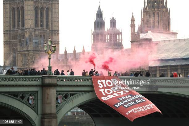 TOPSHOT AntiBrexit campaigners unfurl a banner on Westminster bridge on November 15 2018 in front of the Houses of Parliament in London British Prime...