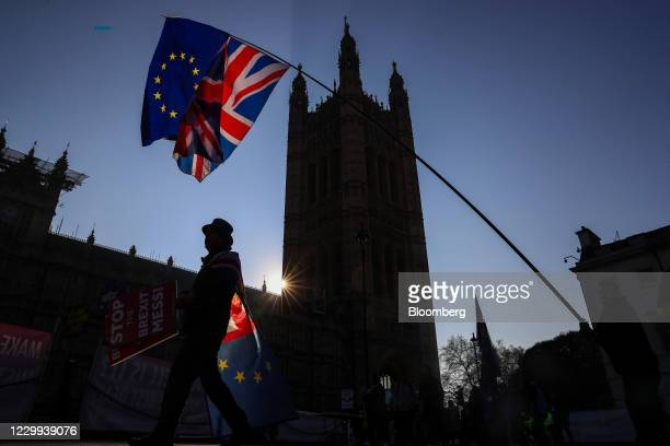Anti-Brexit campaigners wave a European Union flag and a Union Jack, also known as a Union Flag, during a protest near the Houses of Parliament in...