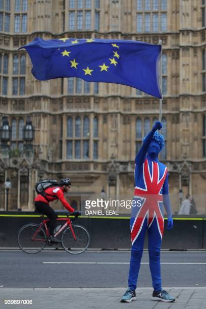 A antiBrexit demonstrator dressed in a Union Flag suit and waving an EU flag stands on the road outside the Houses of Parliament in central London on...