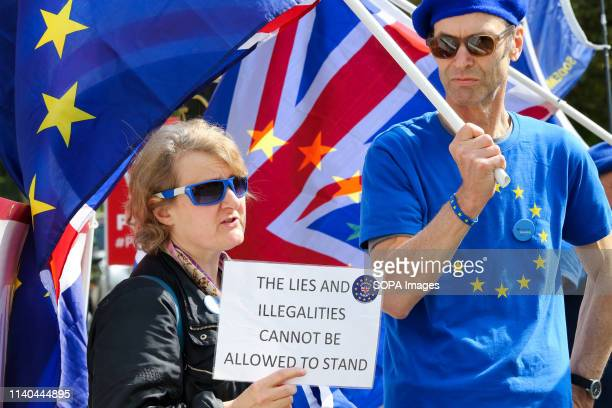 Anti-Brexit demonstrators are seen protesting with placards and flags outside the Houses of Parliament. Ongoing protest about UK leaving the EU.