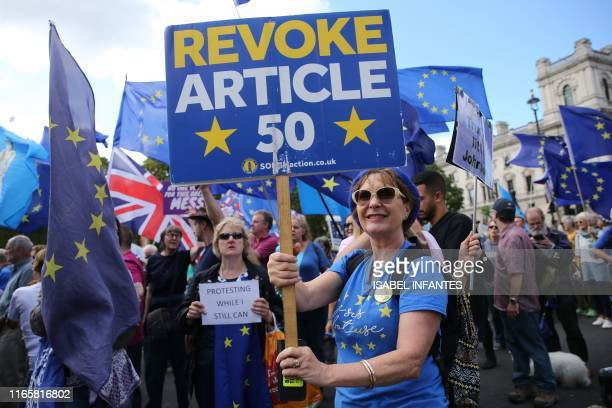 TOPSHOT AntiBrexit demonstrators hold up placards as they march outside the Houses of Parliament in central London on September 3 2019 The fate of...
